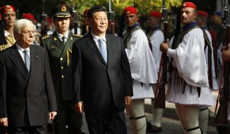 China's President Xi Jinping, centre and his Greek counterpart Prokopis Pavlopoulos, left, inspect the guard of honor by Evzones, the Greek Presidential guards, outside the Presidential palace in Athens, Monday, Nov. 11, 2019. Xi Jinping is in Greece on a two-day official visit. (AP Photos/Thanassis Stavrakis)