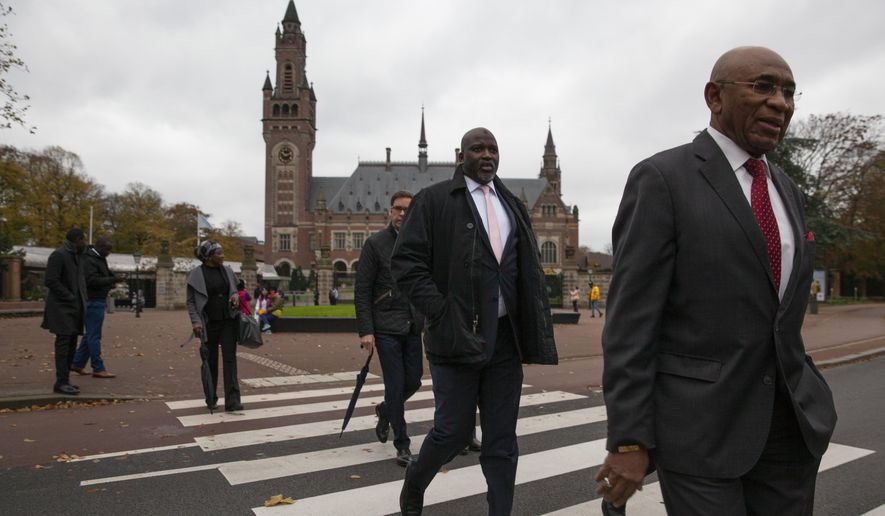 "Gambia's Justice Minister Aboubacarr Tambadou, center, and his delegation leave the Peace Palace, rear, which houses the International Court in The Hague, Netherlands, Monday, Nov. 11, 2019, after filing a case at the United Nations' highest court accusing Myanmar of genocide in its campaign against the Rohingya Muslim minority. A statement released Monday by lawyers for Gambia says the case also asks the International Court of Justice to order measures ""to stop Myanmar's genocidal conduct immediately."" (AP Photo/Peter Dejong)"