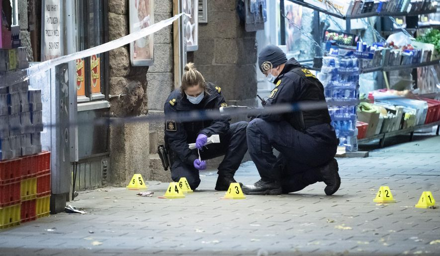 In this photo taken late Saturday, Nov. 9, 2019, police officers work near the scene of a shooting, in Malmo, Sweden. A 15-year-old boy was killed and another teenager was in critical condition after a shooting in a busy square in the southern city of Malmo, Swedish police said Sunday. Similar incidents and explosions in Malmo recently have alarmed politicians and residents. (Johan Nilsson/TT News Agency via AP)