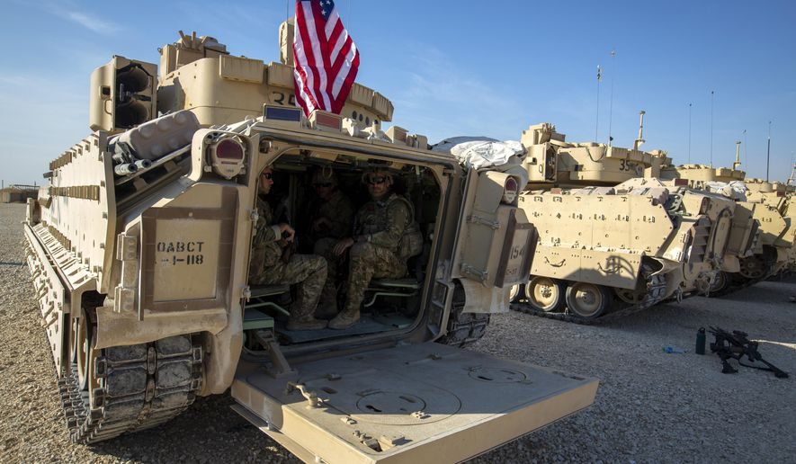 Crewmen sit inside Bradley fighting vehicles at a US military base at an undisclosed location in Northeastern Syria, Monday, Nov. 11, 2019. The deployment of the mechanized force comes after US troops withdrew from northeastern Syria, making way for a Turkish offensive that began last month. (AP Photo/Darko Bandic)