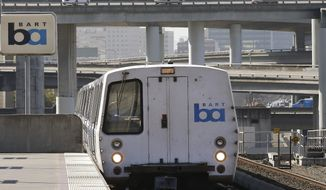 FILE - In this Oct. 15, 2013, file photo, a Bay Area Rapid Transit train departs the MacArthur station in Oakland, Calif. The head of the San Francisco Bay Area commuter train system is apologizing to a black rider who was detained and cited by police for eating a breakfast sandwich on a train platform, BART general manager Bob Powers said in a statement Monday, Nov. 11, 2019. (AP Photo/Ben Margot, File)