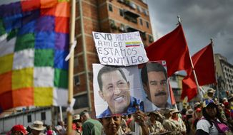 "A supporter of Venezuelan President Nicolas Maduro, whose image is held up at right, and late President Hugo Chavez, left, carries the Spanish message: ""Evo. People. Friend. We are with you"" during a rally in support of former Bolivian President Evo Morales in Caracas, Venezuela, Monday, Nov. 11, 2019. Morales stepped down following weeks of massive protests. (AP Photo/Matias Delacroix)"