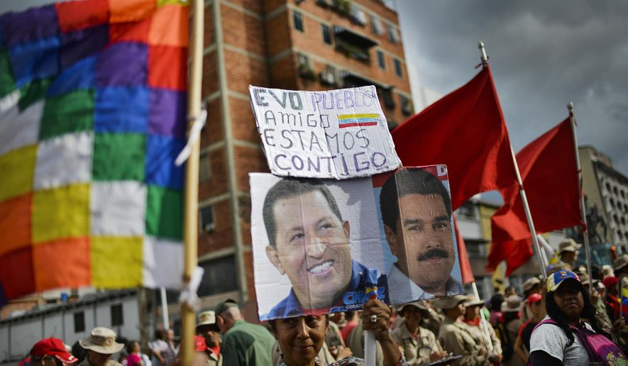 """A supporter of Venezuelan President Nicolas Maduro, whose image is held up at right, and late President Hugo Chavez, left, carries the Spanish message: """"Evo. People. Friend. We are with you"""" during a rally in support of former Bolivian President Evo Morales in Caracas, Venezuela, Monday, Nov. 11, 2019. Morales stepped down following weeks of massive protests. (AP Photo/Matias Delacroix)"""