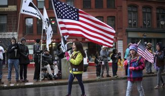 Olivia Robbins carries a large American flag while leading her Girl Scout troop as they march in Veterans Day parade event honoring Mainers who served in the military, Monday, Nov. 11, 2019, in Portland, Maine. (AP Photo/Robert F. Bukaty)