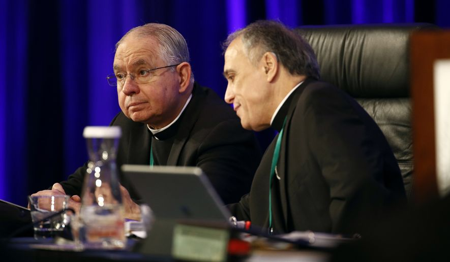 In this Nov. 12, 2018, photo, Archbishop Jose Gomez of Los Angeles, vice president of the United States Conference of Catholic Bishops, left, sits with Cardinal Daniel DiNardo of the Archdiocese of Galveston-Houston, USCCB president, before the conference's annual fall meeting in Baltimore. Gomez overwhelmingly won election Tuesday, Nov. 12, 2019, as the first Hispanic to head the U.S. Conference of Catholic Bishops. (AP Photo/Patrick Semansky) **FILE**