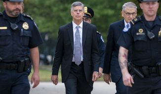 In this Oct. 22, 2019, file photo Ambassador William Taylor, is escorted by U.S. Capitol Police as he arrives to testify before House committees as part of the Democrats impeachment investigation of President Donald Trump, at the Capitol in Washington. (AP Photo/J. Scott Applewhite, File)