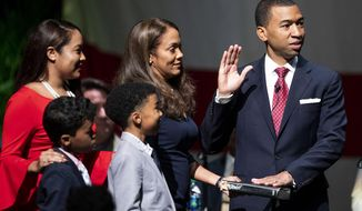 Montgomery Mayor Steven Reed, with his wife Tamika Reed and sons Klein and Karsten and daughter Kyla Cole by his side, is sworn in by Myron Thompson during his inauguration at the Montgomery Performing Arts Center, Tuesday, Nov. 12, 2019, in Montgomery, Ala. (Mickey Welsh/Montgomery Advertiser via AP)