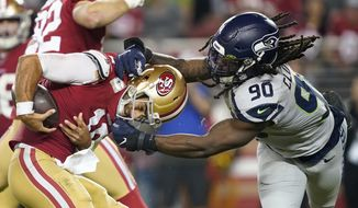 San Francisco 49ers quarterback Jimmy Garoppolo, left, avoids being sacked by Seattle Seahawks defensive end Jadeveon Clowney (90) during the second half of an NFL football game in Santa Clara, Calif., Monday, Nov. 11, 2019. (AP Photo/Tony Avelar)