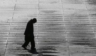A man walks across the icy Legislative Plaza Tuesday, Nov. 12, 2019, in Nashville, Tenn. Snow and icy conditions are snarling traffic and closing or delaying schools in parts of the Northeast and South. (AP Photo/Mark Humphrey)