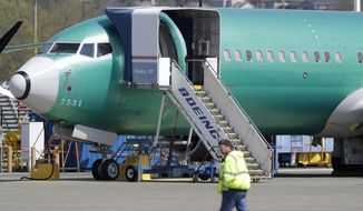 In this April 26, 2019, file photo a worker walks past a Boeing 737 MAX 8 airplane being built for Oman Air at Boeing's assembly facility in Renton, Wash. Orders and deliveries of new Boeing planes remain depressed eight months into the grounding of the company's 737 Max, Boeing said Tuesday, Nov. 12. (AP Photo/Ted S. Warren, File) **FILE**