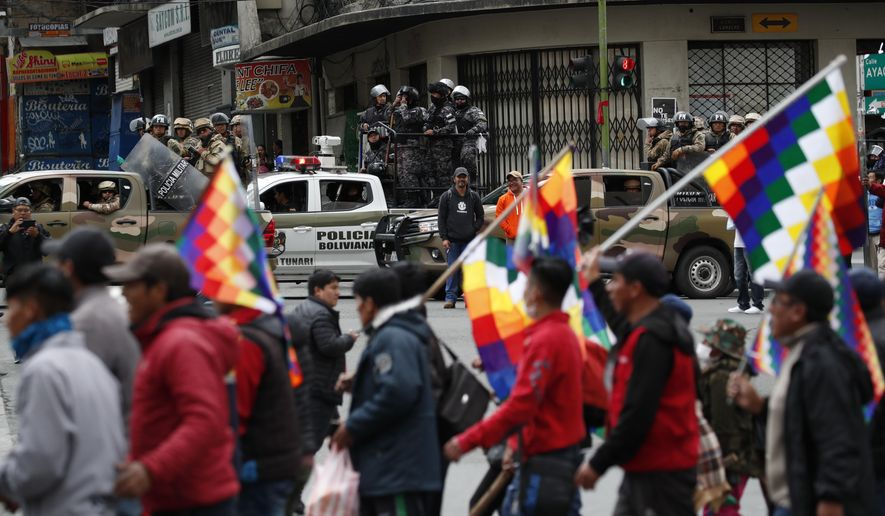 Police patrol on the sidelines of a march by supporters of former President Evo Morales, arriving from El Alto and entering La Paz, Bolivia, Tuesday, Nov. 12, 2019. Former President Evo Morales, who transformed Bolivia as its first indigenous president, flew to exile in Mexico on Tuesday after weeks of violent protests, leaving behind a confused power vacuum in the Andean nation. (AP Photo/Natacha Pisarenko)