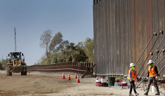 In this Sept. 10, 2019, photo, government contractors erect a section of Pentagon-funded border wall along the Colorado River, in Yuma, Ariz. A federal appeals court hears arguments against diverting Pentagon money for border wall construction as time runs out. It says the Trump administration has moved quickly to spend the money after the Supreme Court rejected an emergency appeal to prevent work from starting in July. (AP Photo/Matt York) **FILE**