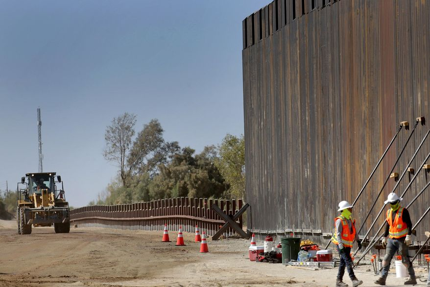 In this Sept. 10, 2019, file photo, government contractors erect a section of Pentagon-funded border wall along the Colorado River, in Yuma, Ariz. (AP Photo/Matt York) **FILE**