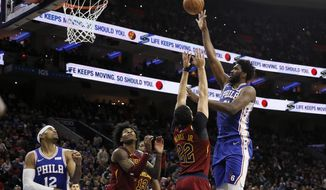 Philadelphia 76ers' Joel Embiid, right, goes up for a shot against Cleveland Cavaliers' Larry Nance Jr. during the first half of an NBA basketball game, Tuesday, Nov. 12, 2019, in Philadelphia. (AP Photo/Matt Slocum)