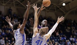 Central Arkansas guard Collin Cooper passes as Duke center Vernon Carey Jr. (1) and forward Jack White (41) guard during the half of an NCAA college basketball game in Durham, N.C., Tuesday, Nov. 12, 2019. (AP Photo/Gerry Broome)