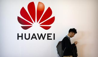 FILE - In this Oct. 31, 2019, filer photo, a man uses his smartphone as he stands near a billboard for Chinese technology firm Huawei at the PT Expo in Beijing. On Tuesday, Nov. 12, 2019, Huawei announced it is paying its workers bonuses as thanks for helping the Chinese tech giant cope with U.S. sanctions threatening its smartphone and other businesses. (AP Photo/Mark Schiefelbein, File)