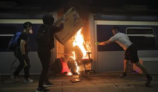 Students burn a train inside the Chinese University MTR station in Hong Kong, Wednesday, Nov. 13, 2019. Protesters in Hong Kong battled police on multiple fronts on Tuesday, from major disruptions during the morning rush hour to a late-night standoff at a prominent university, as the 5-month-old anti-government movement takes an increasingly violent turn. (AP Photo/Kin Cheung)