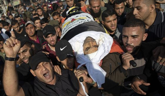 Palestinians chant angry slogans as they carry the body of Islamic Jihad commander, Bahaa Abu el-Atta, who was killed with his wife by an Israeli missile strike hit his house early morning, during his funeral in Gaza City, Tuesday, Nov. 12, 2019. (AP Photo/Khalil Hamra)