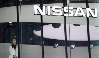 In this July 25, 2019, photo, a staff member stands by a window of a Nissan car gallery in Tokyo. Japanese automaker Nissan has seen July-September profit tumble to half of what it earned the previous year as sales and brand power crumbled since the arrest of former Chairman Carlos Ghosn a year ago. (AP Photo/Eugene Hoshiko)