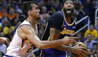 Los Angeles Lakers forward Anthony Davis (3) drives on Phoenix Suns forward Dario Saric in the first half during an NBA basketball game, Tuesday, Nov. 12, 2019, in Phoenix. (AP Photo/Rick Scuteri)