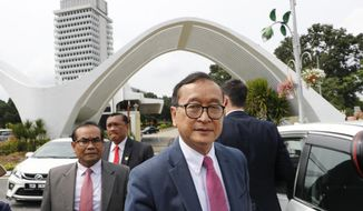 Cambodia's exiled opposition leader Sam Rainsy is asked for comments outside Parliament House in Kuala Lumpur, Malaysia, Tuesday, Nov. 12, 2019. Rainsy landed in Kuala Lumpur in a bid to return to his homeland after Thailand had earlier blocked him from entering. (AP Photo/Vincent Thian)