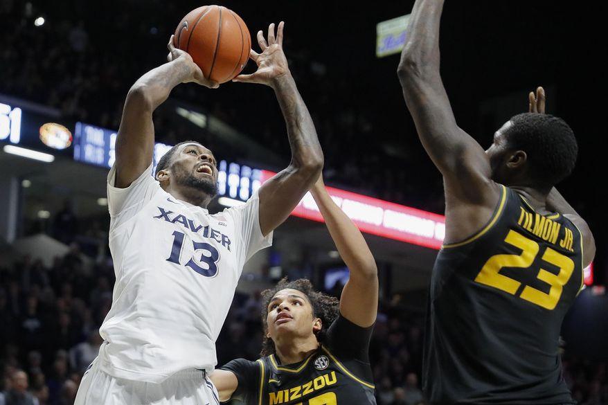 Xavier's Naji Marshall (13) shoots next to Missouri's Jeremiah Tilmon (23) during overtime of an NCAA college basketball game Tuesday, Nov. 12, 2019, in Cincinnati. (AP Photo/John Minchillo)