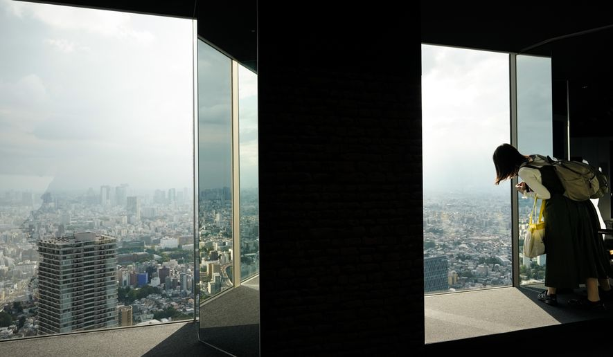 A woman leans over to view the cityscape of Tokyo at Sky Circus Sunshine 60 observatory Monday, Oct. 7, 2019, in Tokyo. (AP Photo/Jae C. Hong)