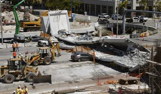 FILE - In this March 16, 2018, file photo, crushed cars lie under a section of a collapsed pedestrian bridge near Florida International University in Miami. Federal transportation officials have concluded that design flaws and a lack of oversight led to the collapse of the pedestrian bridge that killed six people last year. (AP Photo/Wilfredo Lee, File)