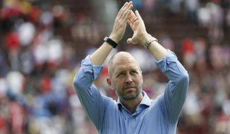 """FILE - In this June 9, 2019, file photo, United States head coach Gregg Berhalter responds to fans after an international friendly soccer match against the Venezuela, in Cincinnati. The sporting director of the U.S. Soccer Federation says Gregg Berhalter's job is safe as men's national team coach despite some disappointing results. """"When I evaluate Gregg and the coaching staff and what I've seen to date, I'm a pleased man, and an individual result is not going to change that. It's just not,"""" sporting director Earnie Stewart said during a telephone conference call with reporters Tuesday, Nov. 12, 2019. (AP Photo/John Minchillo, File)"""
