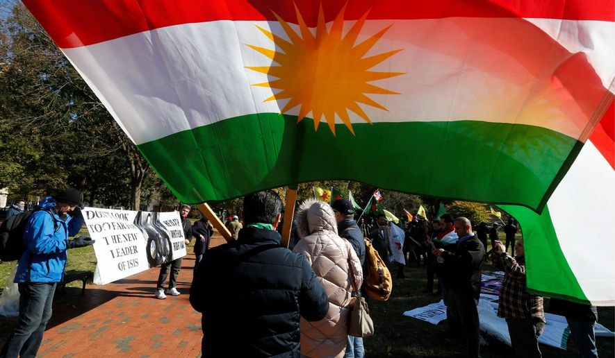 Protesters hold flags and signs before their rally against Turkish President Recep Tayyip Erdogan, who met with President Trump at the White House on Wednesday. (Associated Press)