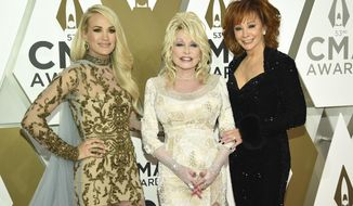 Carrie Underwood, from left, Dolly Parton, and Reba McEntire arrive at the 53rd annual CMA Awards at Bridgestone Arena on Wednesday, Nov. 13, 2019, in Nashville, Tenn. (Photo by Evan Agostini/Invision/AP)
