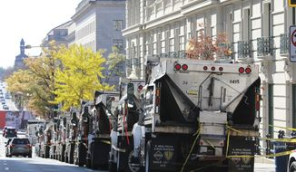 Dump trucks are lined up as part of the security in front of the Willard Hotel where Turkish President Recep Tayyip Erdogan is staying near the White House in Wednesday, Nov. 13, 2019, in Washington. (AP Photo/Steve Helber)