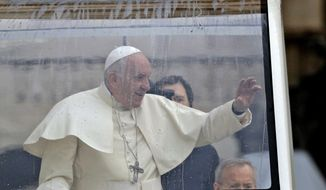 Pope Francis waves as he arrives in his pope mobile, covered with a roof to protect him from the rain, for his weekly general audience in St. Peter's Square, at the Vatican, Wednesday, Nov. 13, 2019. (AP Photo/Gregorio Borgia)