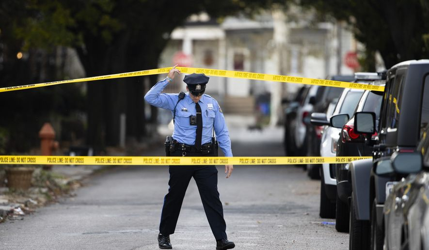 An officer enters the cordoned off the scene of a shooting in Philadelphia, Monday, Nov. 11, 2019. Philadelphia police are questioning a 19-year-old man in the fatal shooting of his 11-year-old brother. The boy was shot in the chest around noon at his home in West Philadelphia. He died at a hospital. (AP Photo/Matt Rourke)