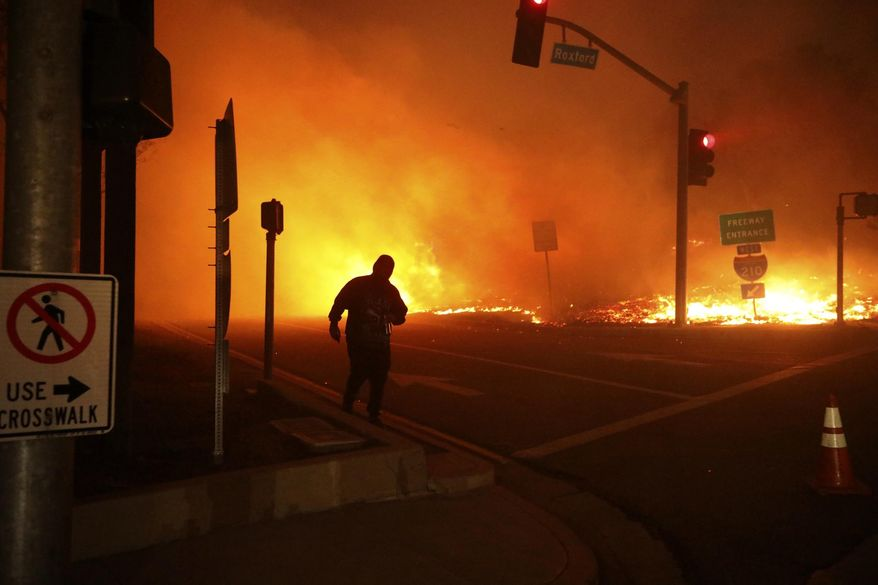 FILE - In this Oct. 11, 2019 file photo, a bystander watches the Saddleridge Fire in Sylmar, Calif. California regulators are voting Wednesday, Nov. 13, on whether to open an investigation into pre-emptive power outages that blacked out large parts of the state for much of October as strong winds sparked fears of wildfires. Pacific Gas & Electric Co. officials insisted on the shut-offs to prevent wildfires but a parade of public officials complained the company botched its communications. (AP Photo/David Swanson, File)
