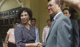 E.U. Ambassador to Cambodia Carmen Moreno, left, shakes hands with the banned Cambodia National Rescue Party's President Kem Sokha before a meeting at his house in Phnom Penh, Cambodia, Wednesday, Nov. 13, 2019. Kem Sokha was freed Sunday by court order after more than two years in detention without trial. (AP Photo/Heng Sinith)