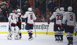 Washington Capitals' Braden Holtby (70) celebrates with Nicklas Backstrom (19) and Alex Ovechkin (8) after winning a shootout in an NHL hockey game against the Philadelphia Flyers, Wednesday, Nov. 13, 2019, in Philadelphia. Washington won 2-1. (AP Photo/Matt Slocum)
