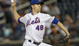 FILE - In this Sept. 9, 2019, file photo, New York Mets starting pitcher Jacob deGrom winds up during the first inning of the team's baseball game against the Arizona Diamondbacks in New York. Mets' deGrom has been named the NL Cy Young Award winner for the second straight year. (AP Photo/Kathy Willens, File)