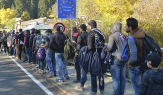 FILE - In this Wednesday, Oct. 28, 2015 file photo German federal police officers guide a group of migrants on their way after crossing the border between Austria and Germany in Wegscheid near Passau, Germany. A new study estimates that at least 3.9 million unauthorized migrants, and possibly as many as 4.8 million, lived in Europe in 2017 with half of them in Germany and the United Kingdom.  (AP Photo/Kerstin Joensson, file)