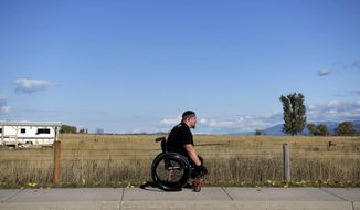 In this Aug. 7, 2019 photo, Thomas (Tomy) Parker, a 29-year-old Marine Corp veteran and triple amputee, trains and gets exercise near downtown Ronan, Mont. The Montana Marine who lost his legs to an IED in Afghanistan came home to a hero's welcome and a house was built for him, but he lost it to addiction. Parker attended rehab, is being treated for PTSD and is now competing in wheelchair races. Parker often wears the same orange pants he was issued while serving time for possession of methamphetamine and heroin. (Tommy Martino/The Missoulian via AP)