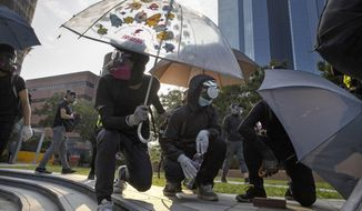Protestors hold umbrellas as they wait for a possible volley of tear gas at the Hong Kong Polytechnic University campus in Hong Kong, Thursday, Nov. 14, 2019. University students from mainland China and Taiwan are fleeing Hong Kong, while those from three Scandinavian countries have been moved or urged to leave as college campuses become the latest battleground in the city's 5-month-long anti-government unrest. (AP Photo/Ng Han Guan)
