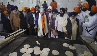 Britain's Prince Charles, center, flips roties or flat Indian bread during his visit to Gurudwara Bangla Sahib, a Sikh Temple in New Delhi, India, Wednesday, Nov. 13, 2019. Prince Charles visited the Sikh temple to participate in celebrations of the 550th birth anniversary of Sikh Guru, Baba Guru Nanak, and mark the contribution of the Sikh community in Britain. During his two day visit he is also meeting with Indian experts focusing on global challenges such as business sustainability and climate change. (AP Photo/Manish Swarup)