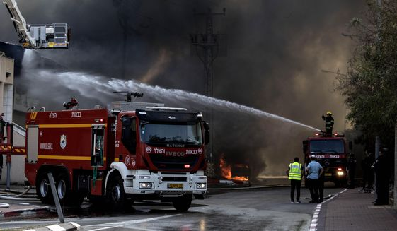 Firefighters deploy after a factory hit by a rocket caught fire in Sderot, southern Israel , Israel, Tuesday, Nov. 12m 2019. Israel has killed a senior Islamic Jihad commander in Gaza in a rare targeted killing that threatened to unleash a fierce round of cross-border violence with Palestinian militants. (AP Photo/Tsafrir Abayov)