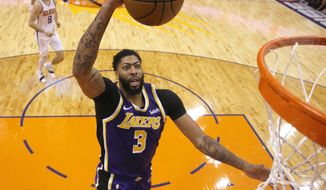 Los Angeles Lakers forward Anthony Davis scores against the Phoenix Suns during the second half during an NBA basketball game Tuesday, Nov. 12, 2019, in Phoenix. (AP Photo/Rick Scuteri)