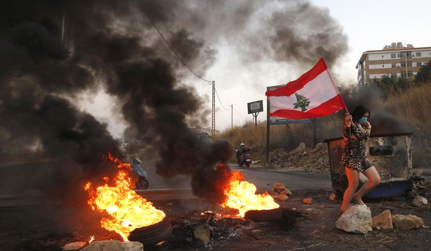 An anti-government protester carries her national flag past burning tires blocking the main highway during protests against the corruption in Khaldeh, south of Beirut, Lebanon, Wednesday, Nov. 13, 2019. A local official for a government political party was shot dead by soldiers trying to open a road closed by protesters in southern Beirut late Tuesday, the army reported, marking the first death in 27 days of nationwide protests. (AP Photo/Hussein Malla)