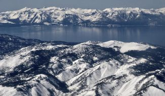 In this March 2, 2017 aerial photo, record winter snowfall is seen in the mountains around Lake Tahoe, viewed from above the Washoe Valley just south of Reno, Nev. Winter recreationists at Lake Tahoe are lining up on opposite sides of Forest Service plans that would close some areas to snowmobiles while opening others currently off limits to motorized use. The Forest Service has extended its public comment period on the snow travel management plan through Dec. 9, 2019. (AP Photo/Scott Sonner, File)
