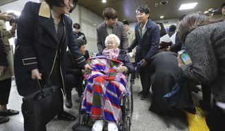 Former South Korean comfort woman Lee Ok-seon, center, leaves the Seoul Central District Court in Seoul, South Korea, Wednesday, Nov. 13, 2019. A Seoul court on Wednesday began hearing a long-awaited civil case filed against the Japanese government by South Korean women who were forced to work in Japan's World War II military brothels. (AP Photo/Ahn Young-joon)
