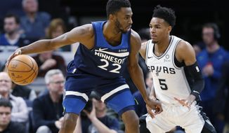 Minnesota Timberwolves' Andrew Wiggins, left, drives around San Antonio Spurs' Dejounte Murray in the first half of an NBA basketball game Wednesday, Nov 13, 2019, in Minneapolis. (AP Photo/Jim Mone)