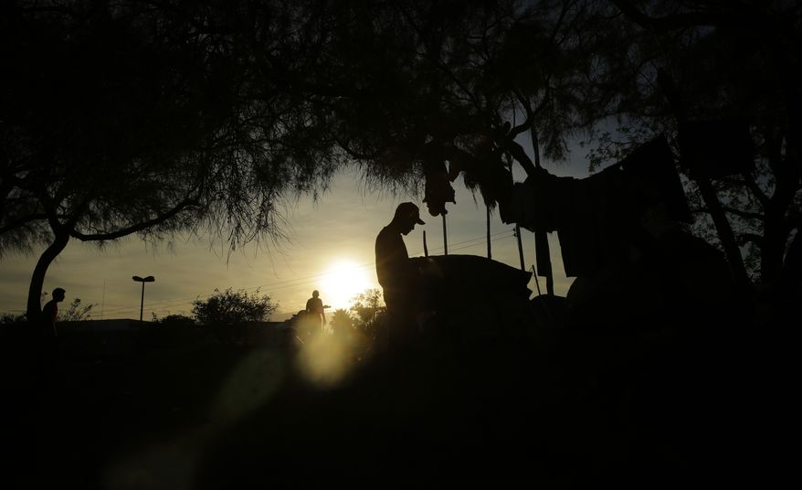 In this Tuesday, Nov. 5, 2019, photo, immigrants waiting for their U.S. court dates live in a refugee camp in Matamoros, Mexico, across from Brownsville, Texas, cooks dinner as the sun sets. The camp is an outgrowth of the Trump administrations Remain in Mexico program, in which more than 55,000 migrants seeking entry into the U.S. have been ordered to pursue their cases outside its borders. (AP Photo/Eric Gay)