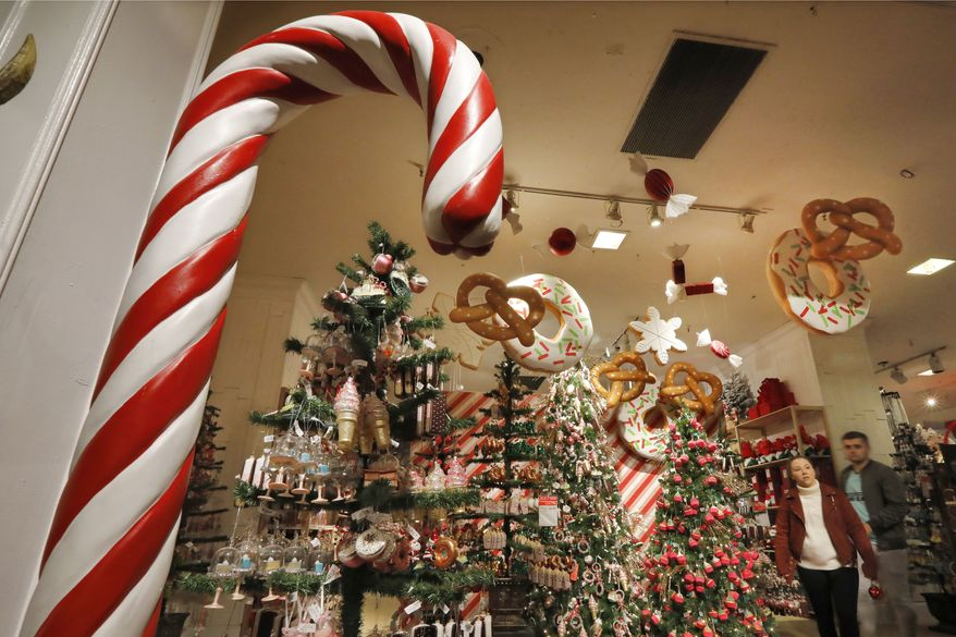 In this Tuesday, Nov. 5, 2019, photo shoppers browse the food-themed decorations in the Holiday Lane section at the Macy's flagship store, in New York. With three weeks until the official start of the holiday shopping season, the nations retailers are gearing up for what will be another competitive shopping period. (AP Photo/Richard Drew)